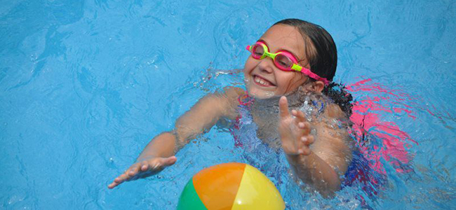 Girl Wearing Goggles Playing in Pool with Ball